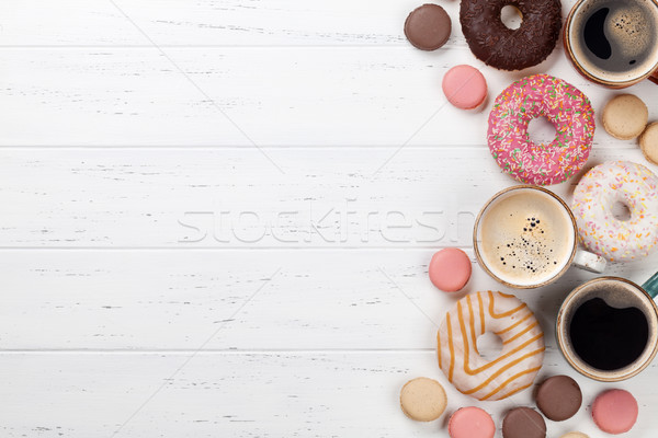 Coffee cups, donuts and macaroons Stock photo © karandaev