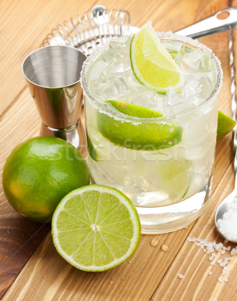 Stock photo: Classic margarita cocktail with salty rim on wooden table