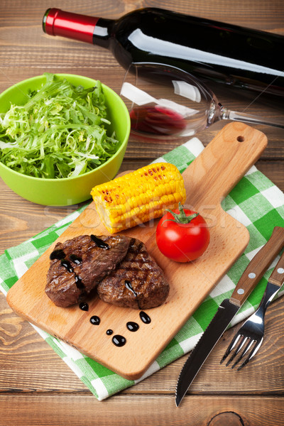 Steak grillés maïs salade vin rouge table en bois Photo stock © karandaev