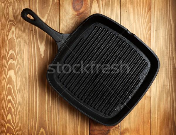 Frying pan on wooden table background Stock photo © karandaev