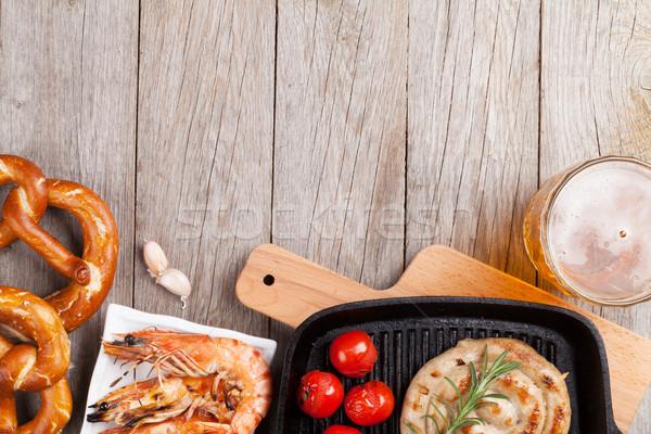 Beer mug, grilled shrimps, sausages and pretzel Stock photo © karandaev