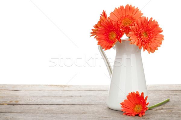 Orange gerbera flowers in pitcher Stock photo © karandaev