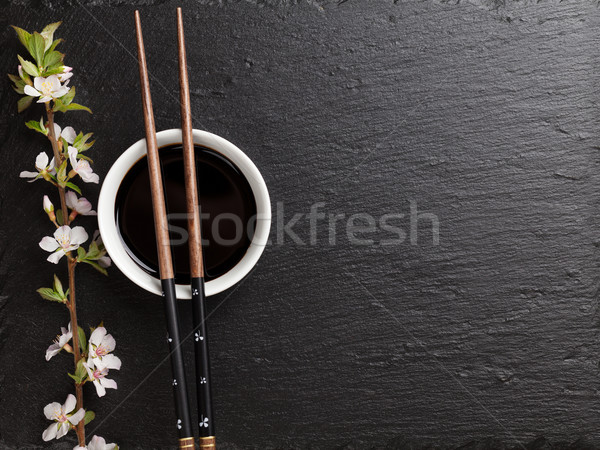 Japanese sushi chopsticks, soy sauce bowl and sakura blossom Stock photo © karandaev