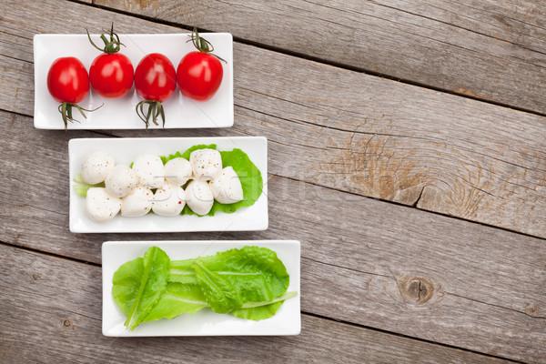 Paradicsomok mozzarella zöld saláta levelek fa asztal Stock fotó © karandaev
