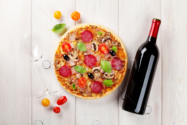 Italian pizza with pepperoni, tomatoes, olives, basil and red wi Stock photo © karandaev