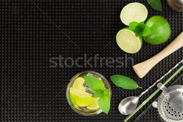 Mojito cocktail and ingredients over black rubber mat Stock photo © karandaev
