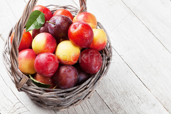 Fresh ripe peaches and plums in basket Stock photo © karandaev
