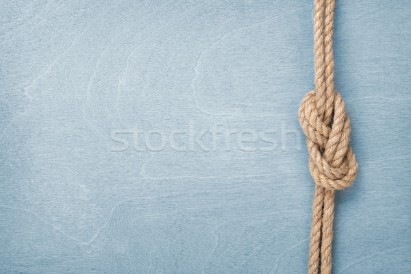 Ship rope knot on wooden texture background Stock photo © karandaev