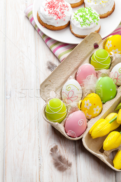 Stock photo: Easter with yellow tulips, colorful eggs and traditional cakes