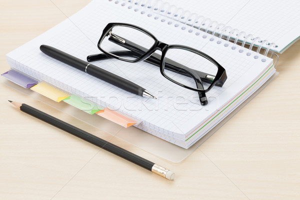 Office table with glasses, blank notepad and pencil Stock photo © karandaev