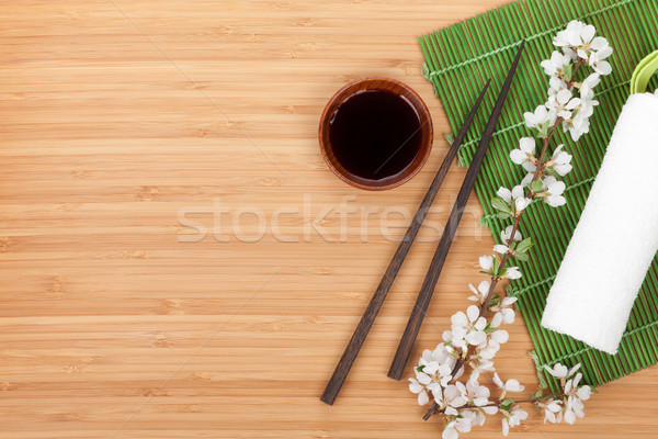 Chopsticks, sakura branch, soy sauce and bamboo mat Stock photo © karandaev