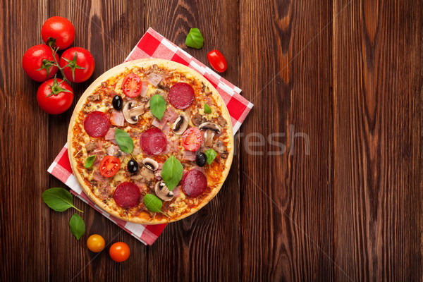 Italian pizza with pepperoni, tomatoes, olives and basil Stock photo © karandaev
