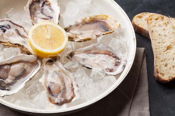 Opened oysters and lemon over ice Stock photo © karandaev