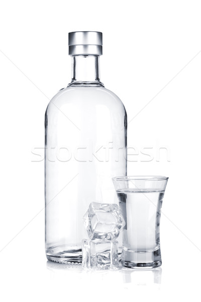 Bottle of vodka and shot glass with ice Stock photo © karandaev