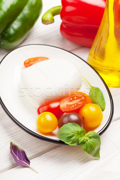 Mozzarella, tomatoes, basil and olive oil Stock photo © karandaev