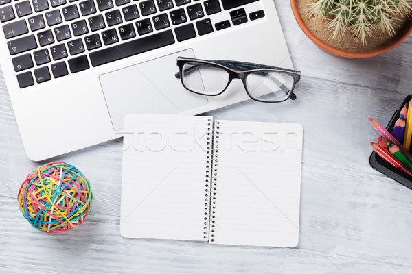 Desk table with laptop and notepad Stock photo © karandaev