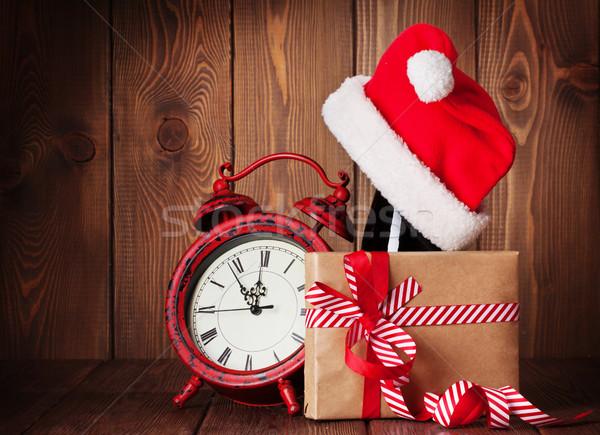 Christmas gift, alarm clock, santa hat and champagne Stock photo © karandaev