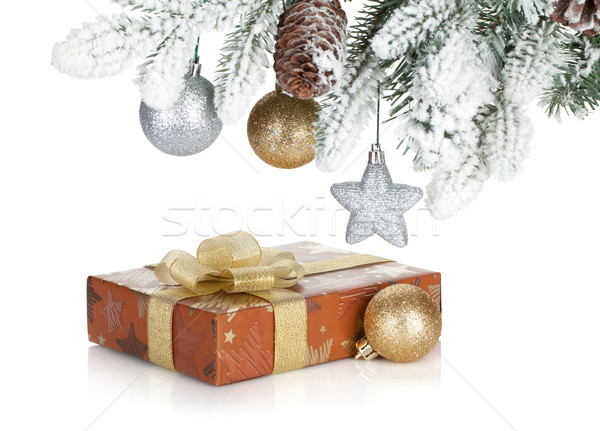 Gift box and christmas decor under snowy fir tree Stock photo © karandaev