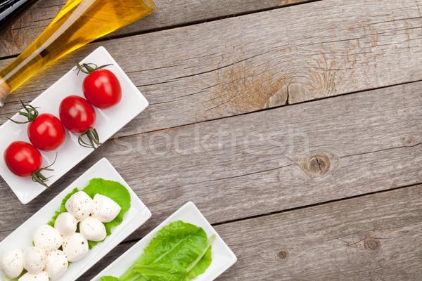 Paradicsomok mozzarella zöld saláta levelek fűszerek Stock fotó © karandaev
