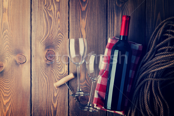 Vinho tinto garrafa óculos rústico mesa de madeira Foto stock © karandaev
