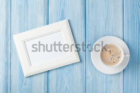 Coffee cup and blank photo frame on wooden table background Stock photo © karandaev