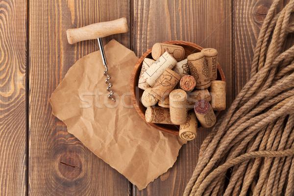 Wine corks and corkscrew over rustic wooden table Stock photo © karandaev