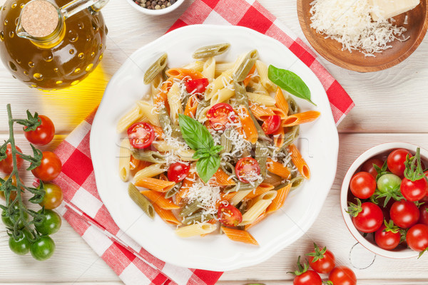 Colorful penne pasta with tomatoes and basil Stock photo © karandaev