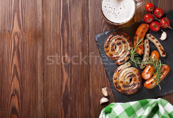 Gegrild worstjes bier mok houten tafel top Stockfoto © karandaev