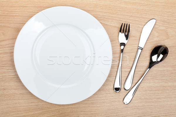 Empty white plate with silverware on wooden table Stock photo © karandaev
