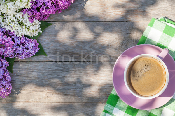 Coffee cup and colorful lilac flowers on garden table Stock photo © karandaev