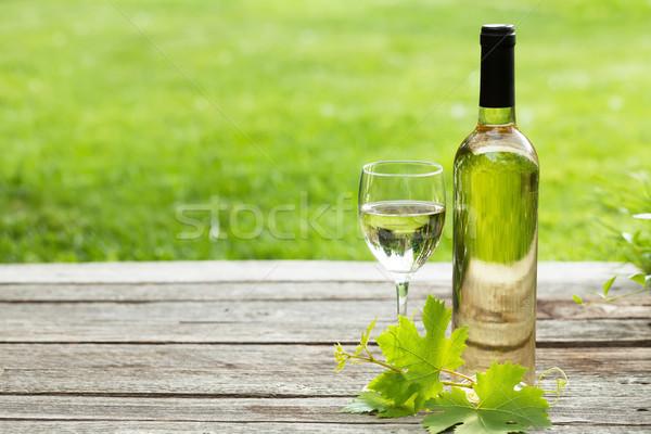 White wine bottle and glass on wooden table Stock photo © karandaev