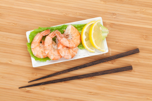 Cooked shrimps with lemon and chopsticks Stock photo © karandaev