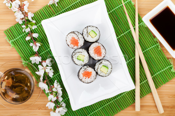 Sushi maki set, green tea and sakura branch Stock photo © karandaev