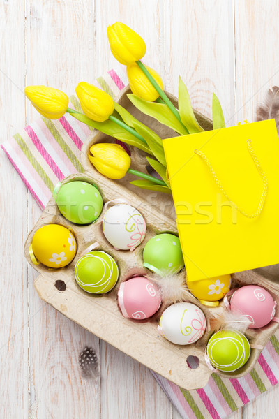 Easter with yellow tulips, colorful eggs and gift bag Stock photo © karandaev