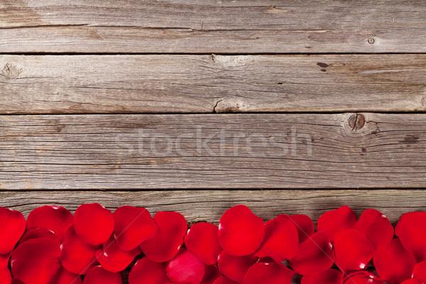Red rose petals over wooden background Stock photo © karandaev