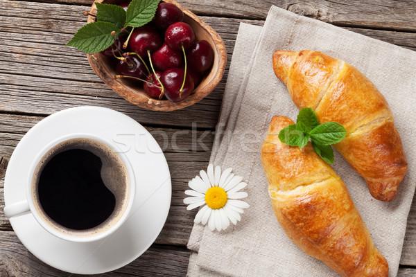 Croissants xícara de café mesa de madeira cerejas topo ver Foto stock © karandaev