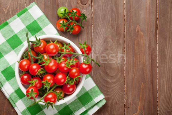 Pomodorini ciotola tavolo in legno top view copia spazio Foto d'archivio © karandaev