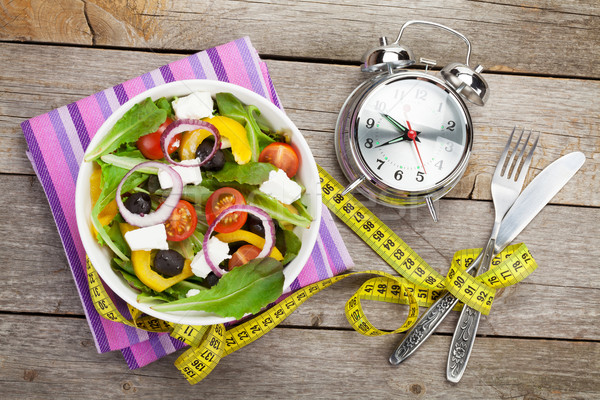 Fresh healthy salad and measuring tape on wooden table Stock photo © karandaev