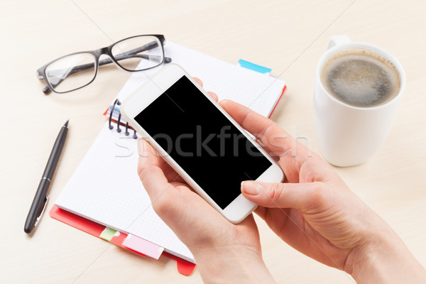 Woman holding smartphone above business desk Stock photo © karandaev