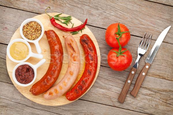 Különböző grillezett kolbászok fűszerek paradicsomok vágódeszka Stock fotó © karandaev