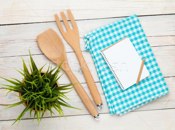 Kitchen utensil and notepad over wooden table Stock photo © karandaev