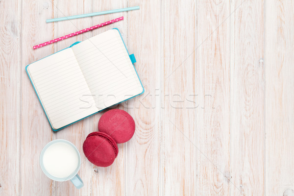Cup of milk and macarons on white wooden table with notepad Stock photo © karandaev