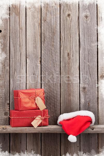 Christmas gift boxes and santa hat Stock photo © karandaev