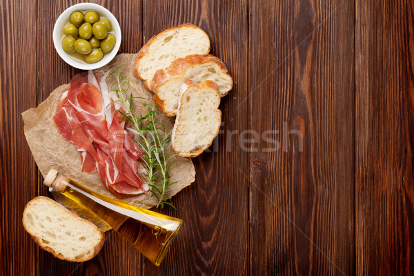 Prosciutto romero aceite de oliva mesa de madera superior vista Foto stock © karandaev