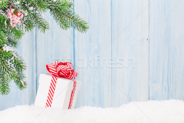 Stock photo: Christmas gift box and fir tree branch in snow