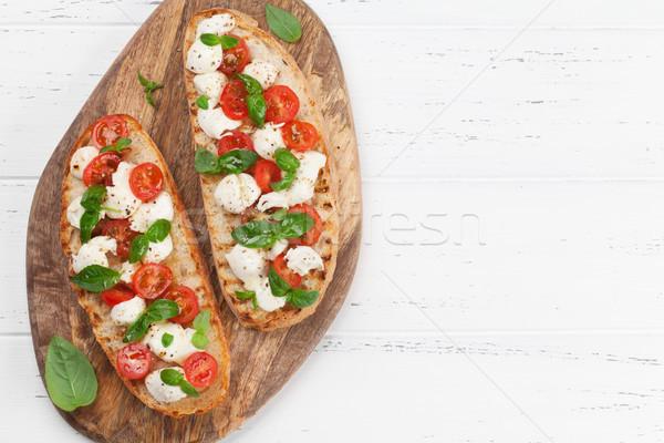 Caprese bruschetta tomates cherry mozzarella albahaca superior Foto stock © karandaev