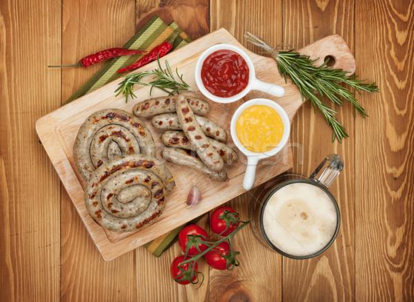 Grillezett kolbászok ketchup mustár bögre sör Stock fotó © karandaev