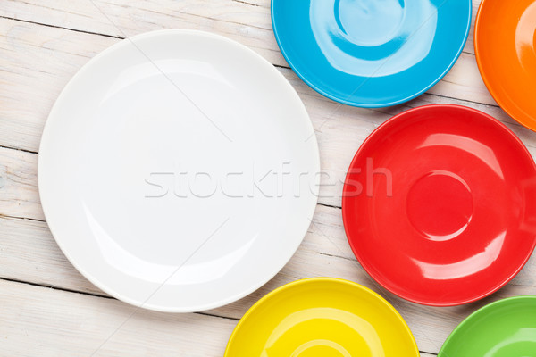 Colorful plates over white wooden table background Stock photo © karandaev
