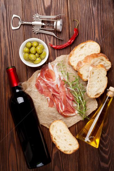 Prosciutto vinho azeitonas parmesão azeite mesa de madeira Foto stock © karandaev