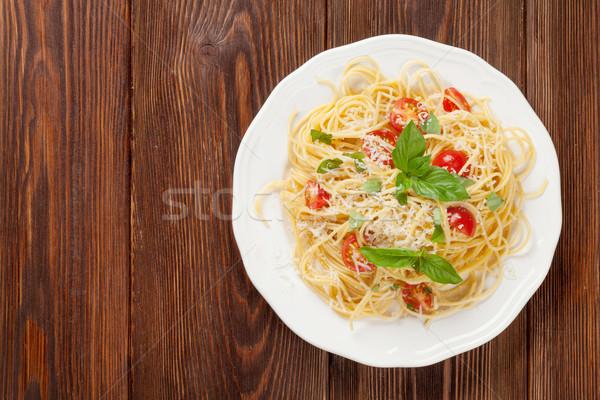 Espaguete macarrão tomates manjericão mesa de madeira topo Foto stock © karandaev